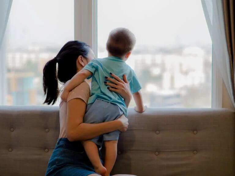 Mãe olhando a rua pela janela com o filho no colo