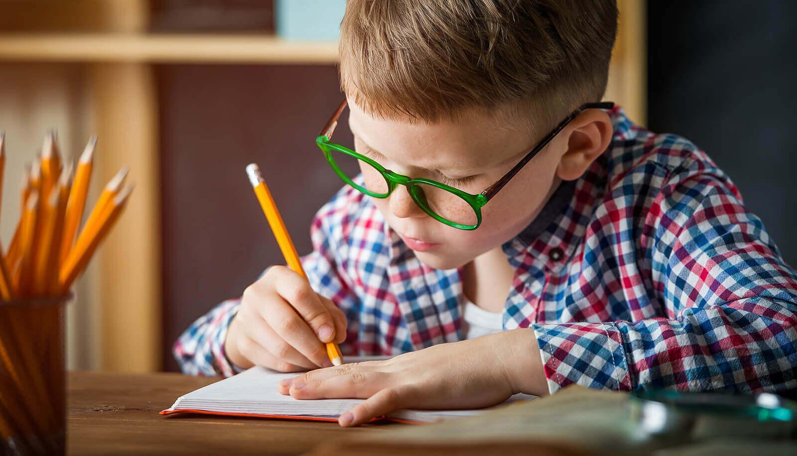Menino aprendendo a escrever à mão.
