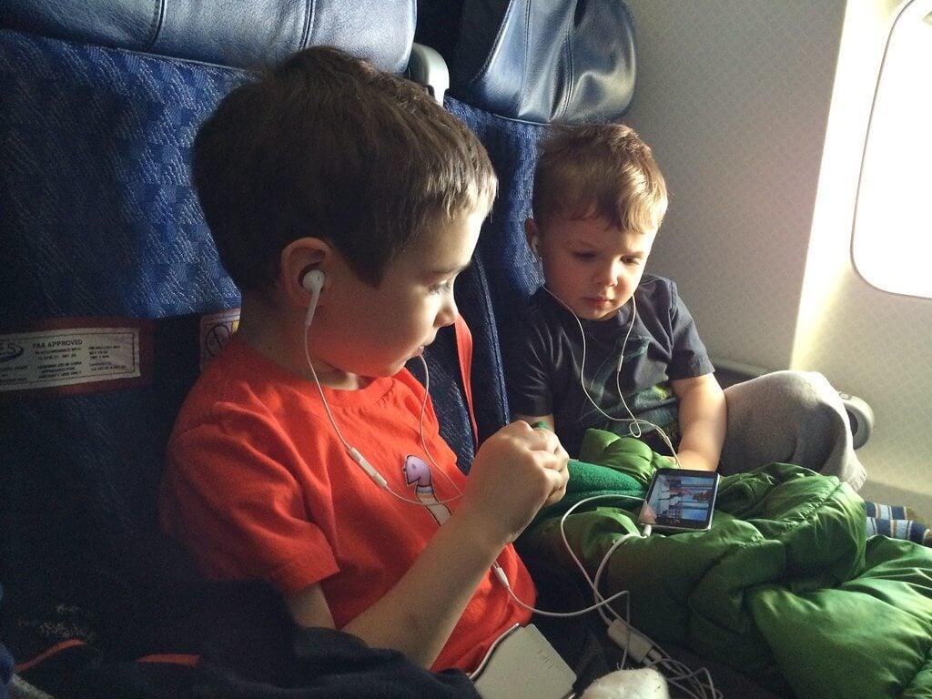 Meninos assistindo no celular dentro do avião.