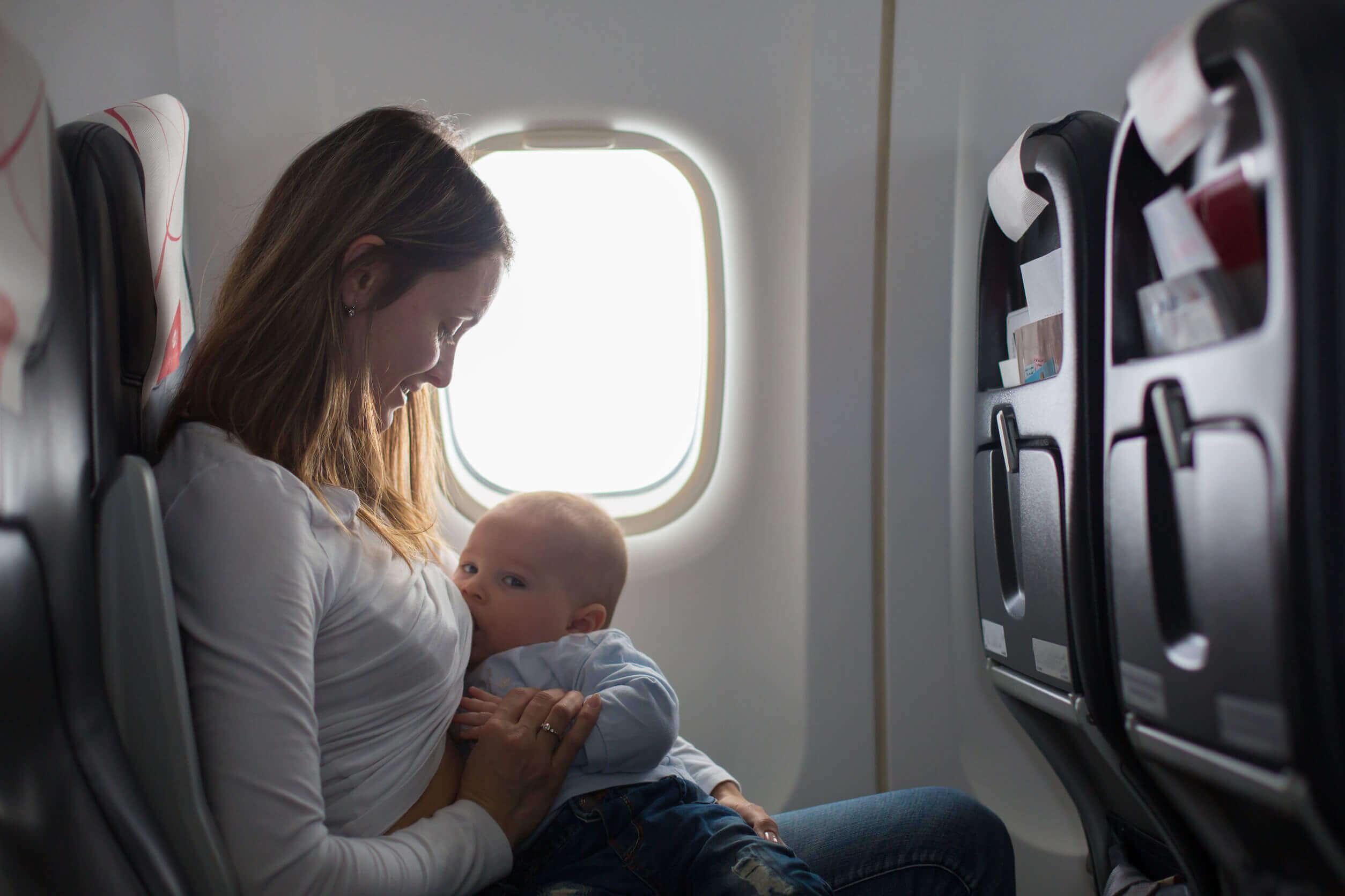 Mulher amamenta seu filho em um avião.