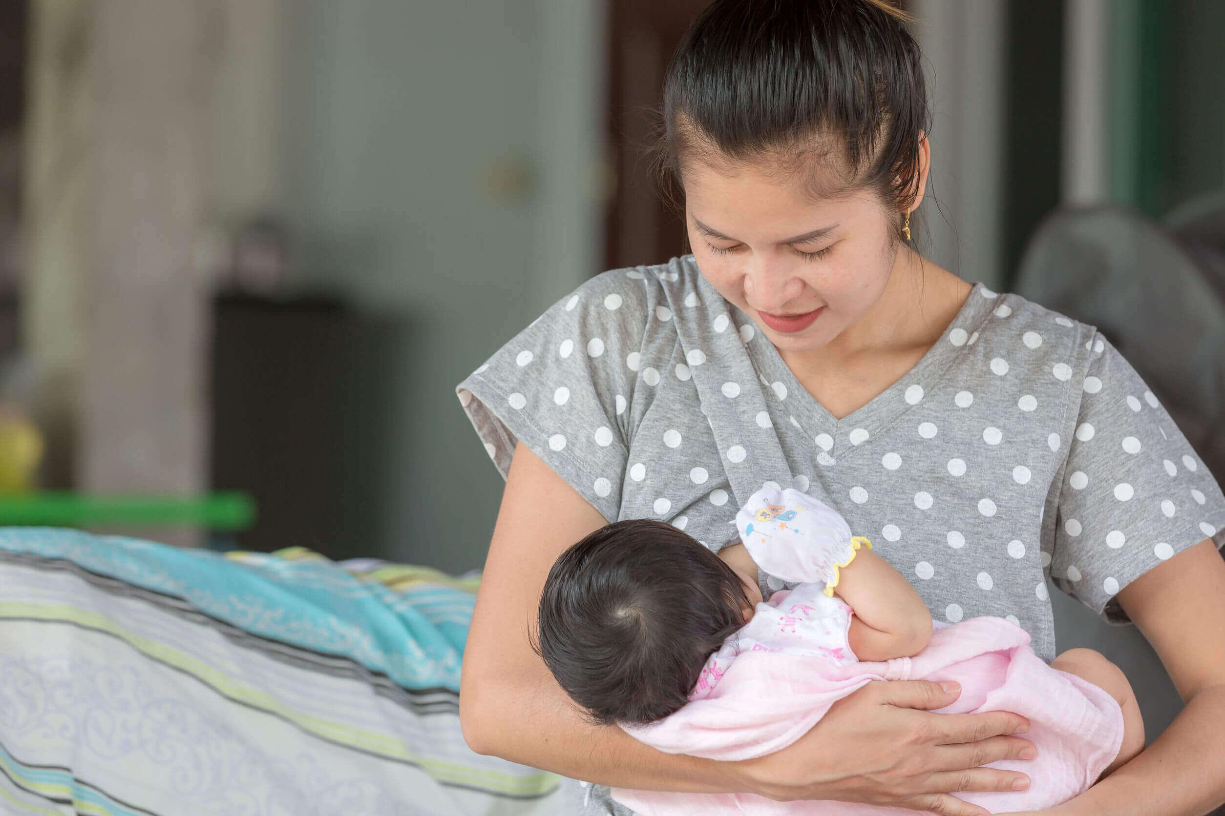 Mãe amamentando seu bebê com protetores de mamilo.