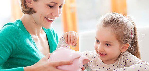 Mãe ensinando filha a poupar com o cofrinho.