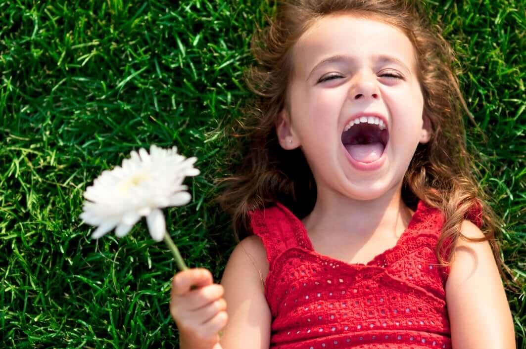 Menina segurando flor sorrindo.