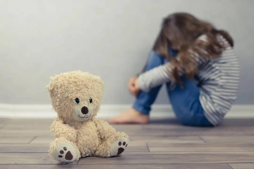Menina muito triste com um ursinho de pelúcia enquanto pensava em suicídio.