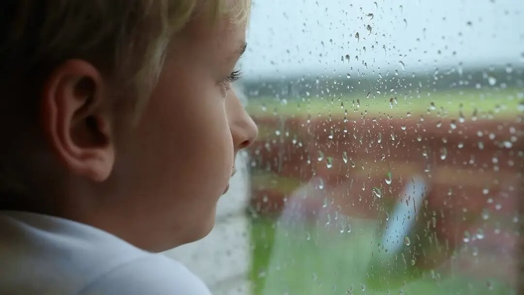 Menino olhando pela janela pensando em suicídio.