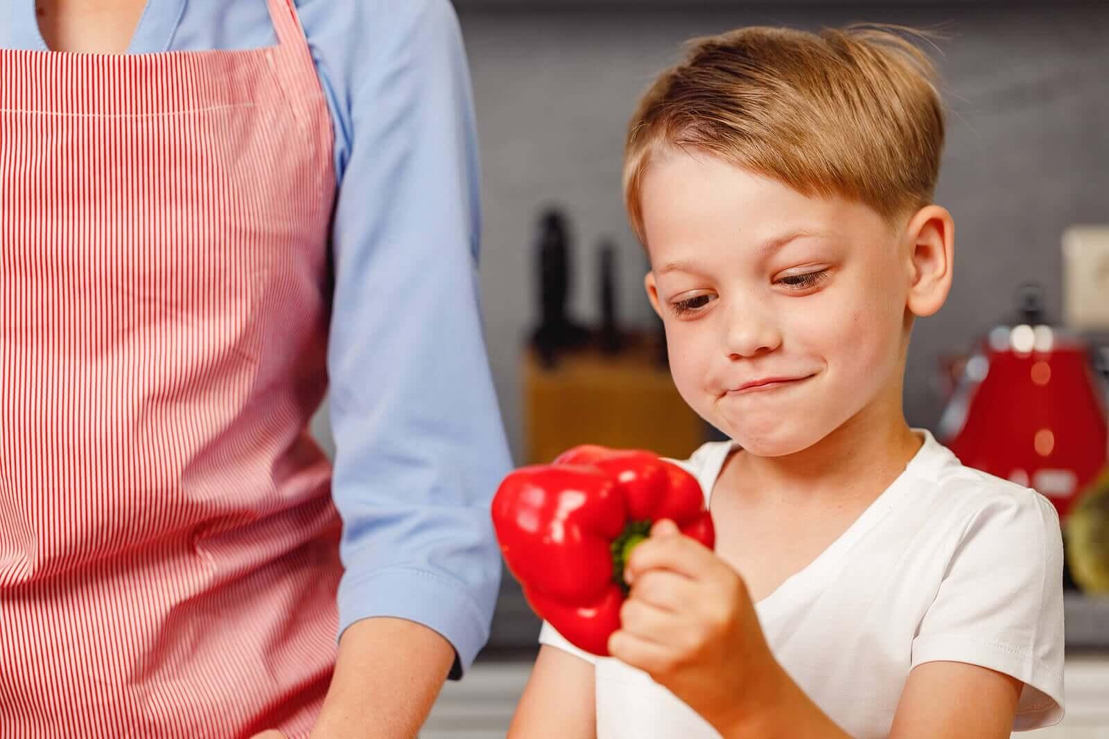 Criança com pimentão na cozinha.