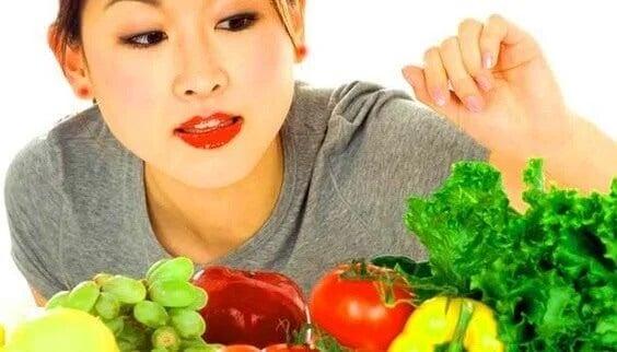 Mulher escolhendo entre frutas e verduras.