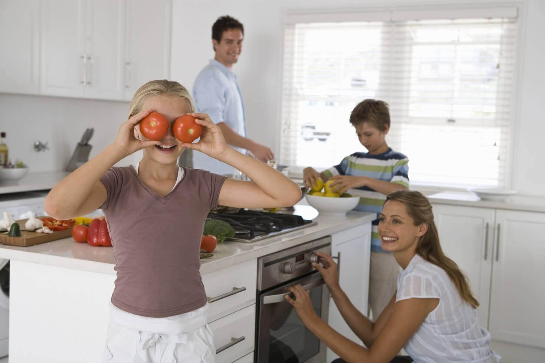 Crianças e adultos se divertindo na cozinha.