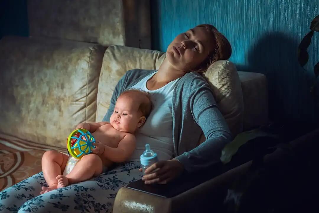 Mãe exausta com o filho nos braços porque não aprendeu a delegar.