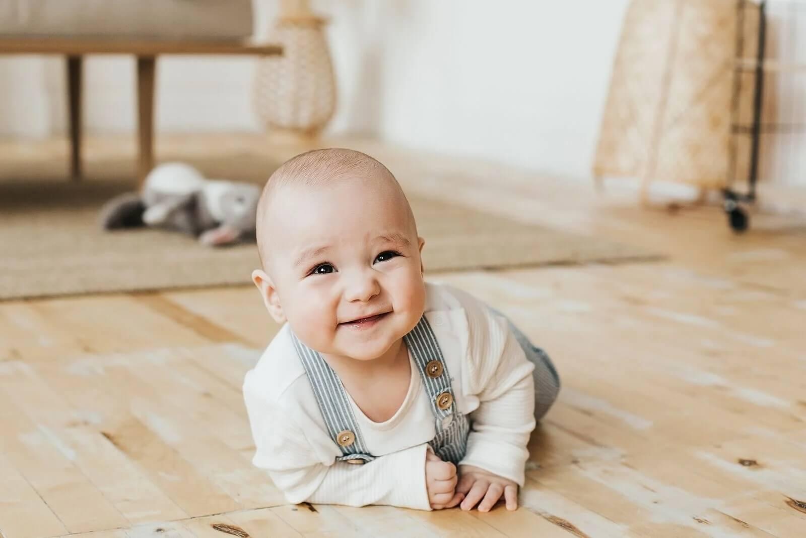 Bebê feliz enquanto engatinha e aprende a ter uma boa higiene postural.