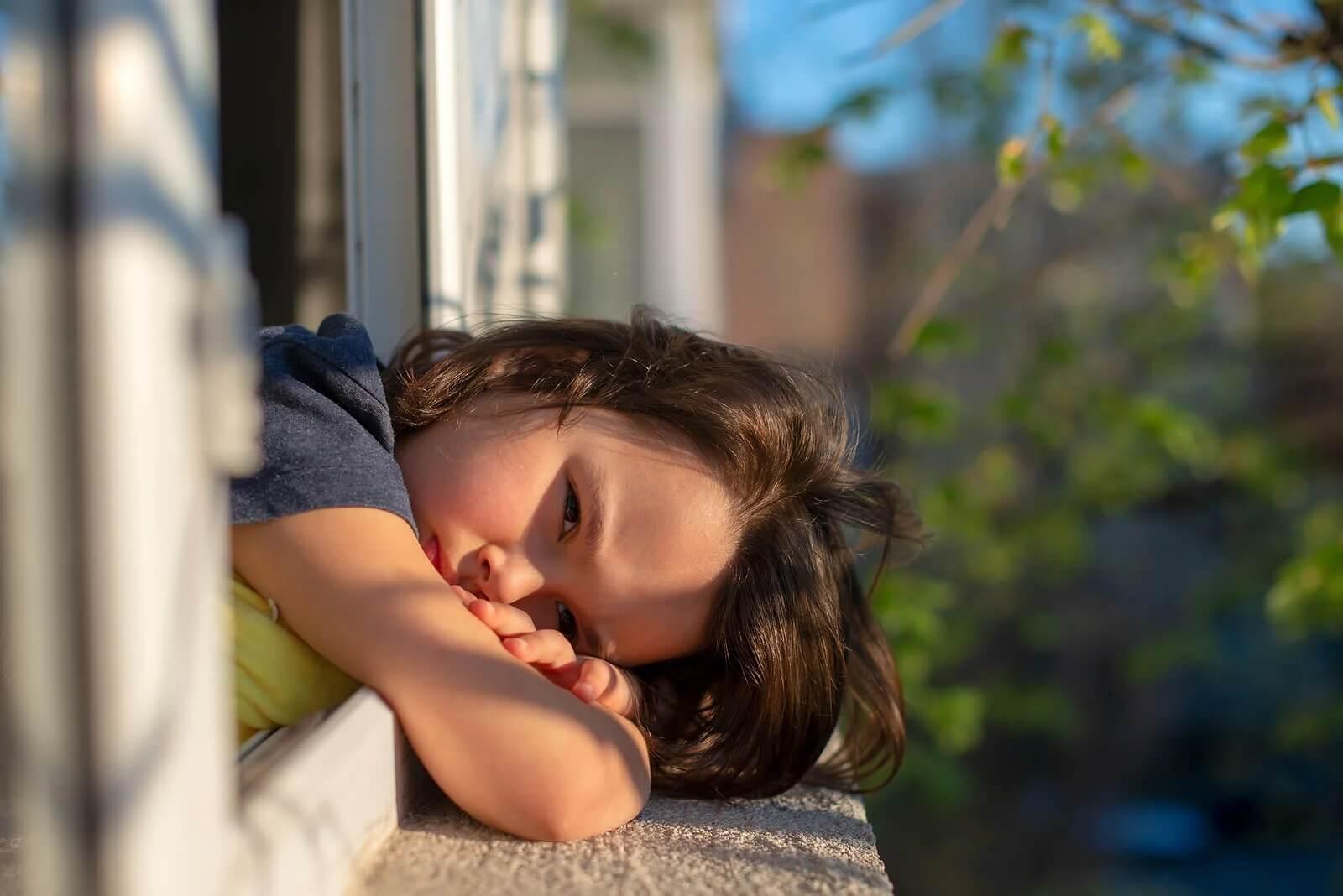 Menina inclinada para fora da janela triste porque não para de reclamar.