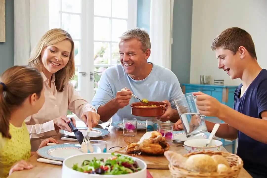 Família comendo com seus filhos levando em consideração a alimentação infantil em etapas.