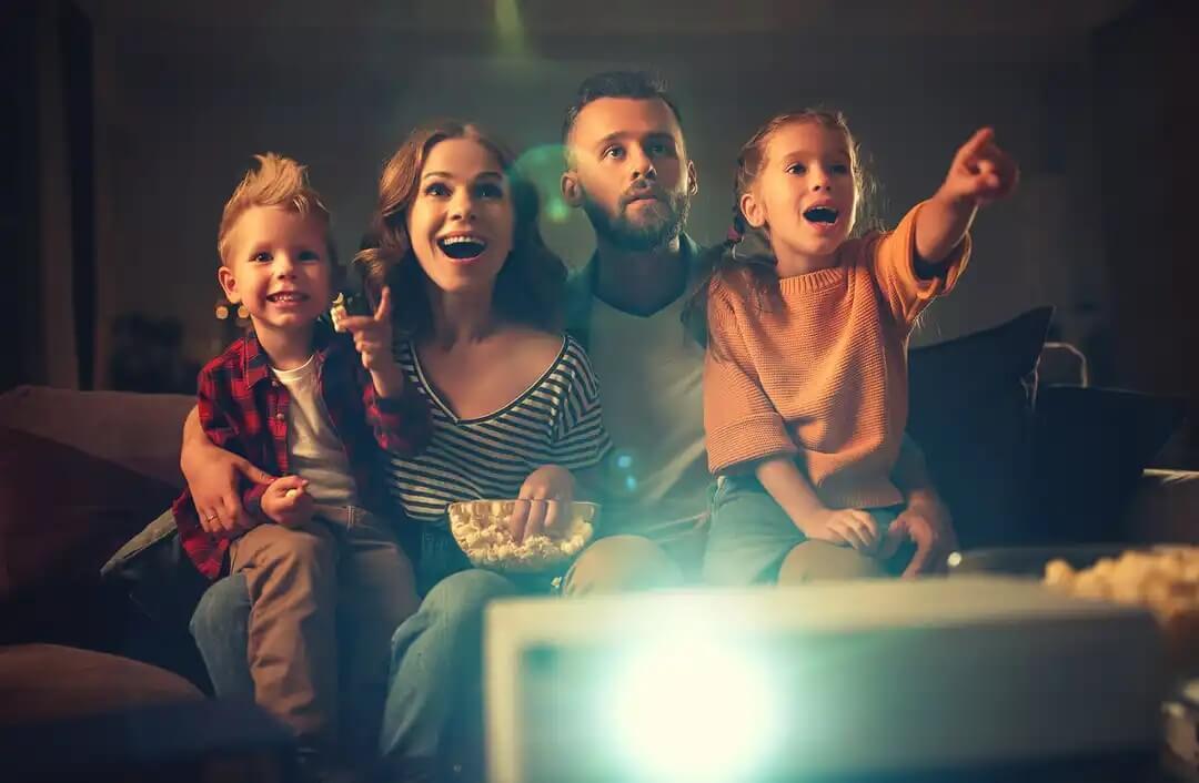 Família assistindo a um filme para criar momentos felizes.