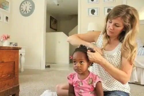 Mãe arrumando cabelo filha.