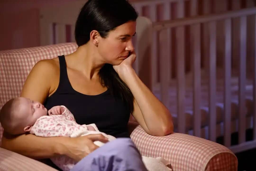 Mulher tentando ajudar seu bebê a dormir à noite.