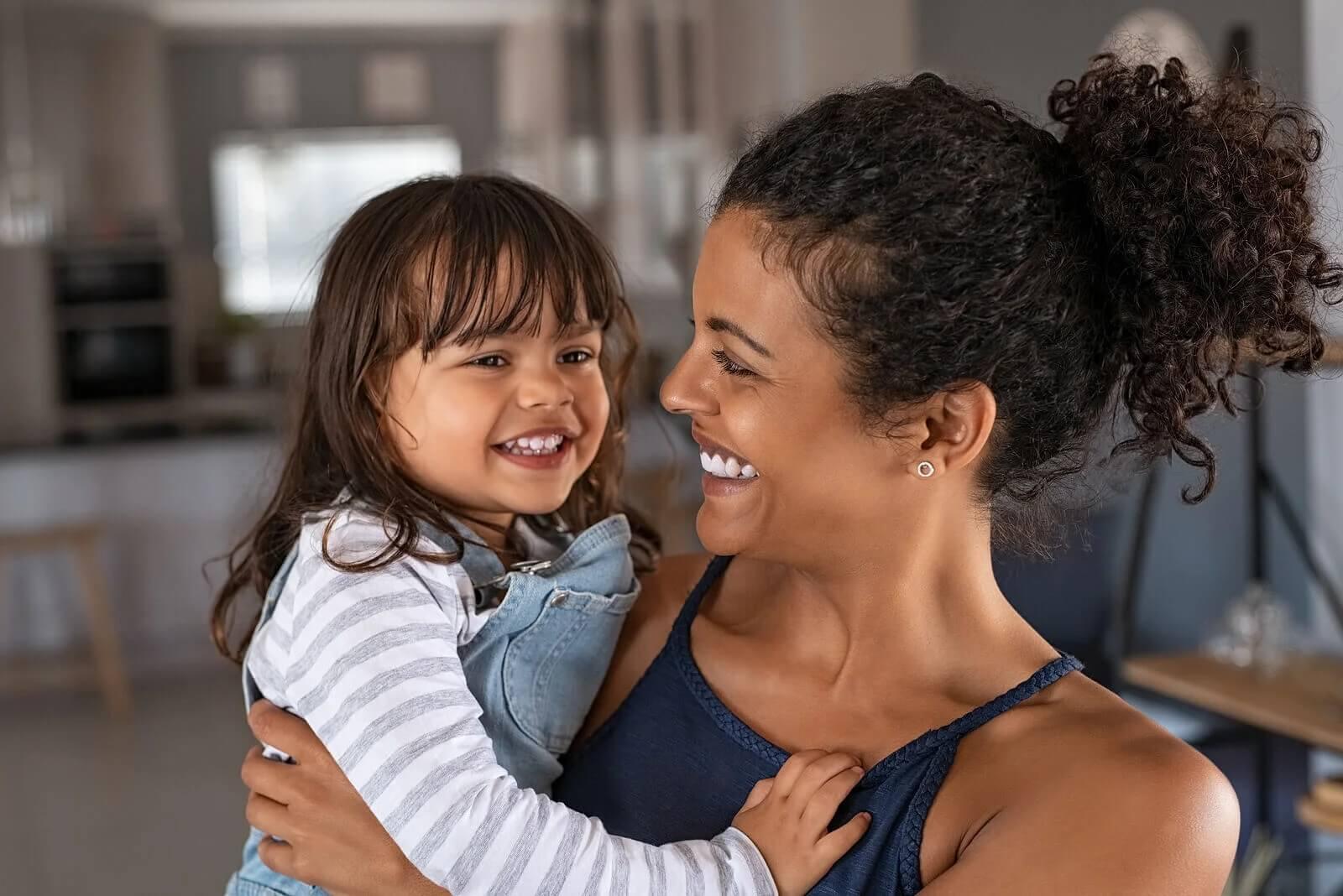 Mãe abraçando a filha e dizendo frases para expressar amor.