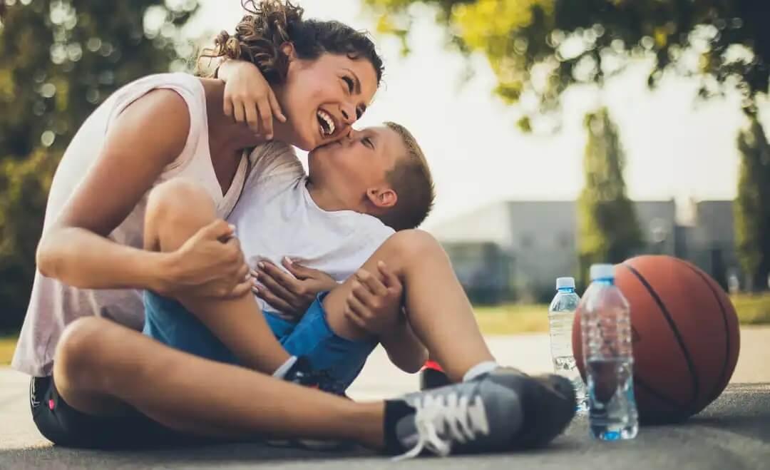 Filho dando um beijo na mãe após jogar basquete, um dos sinais de que seu filho ama você.