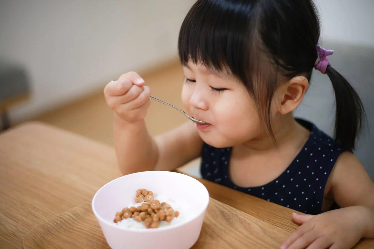 Menina comendo arroz e leguminosas.