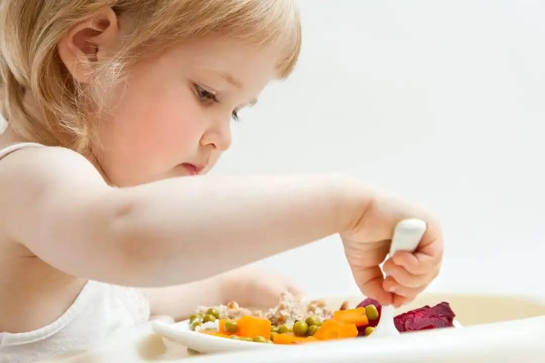 Menina comendo saudável para prevenir transtornos alimentares.