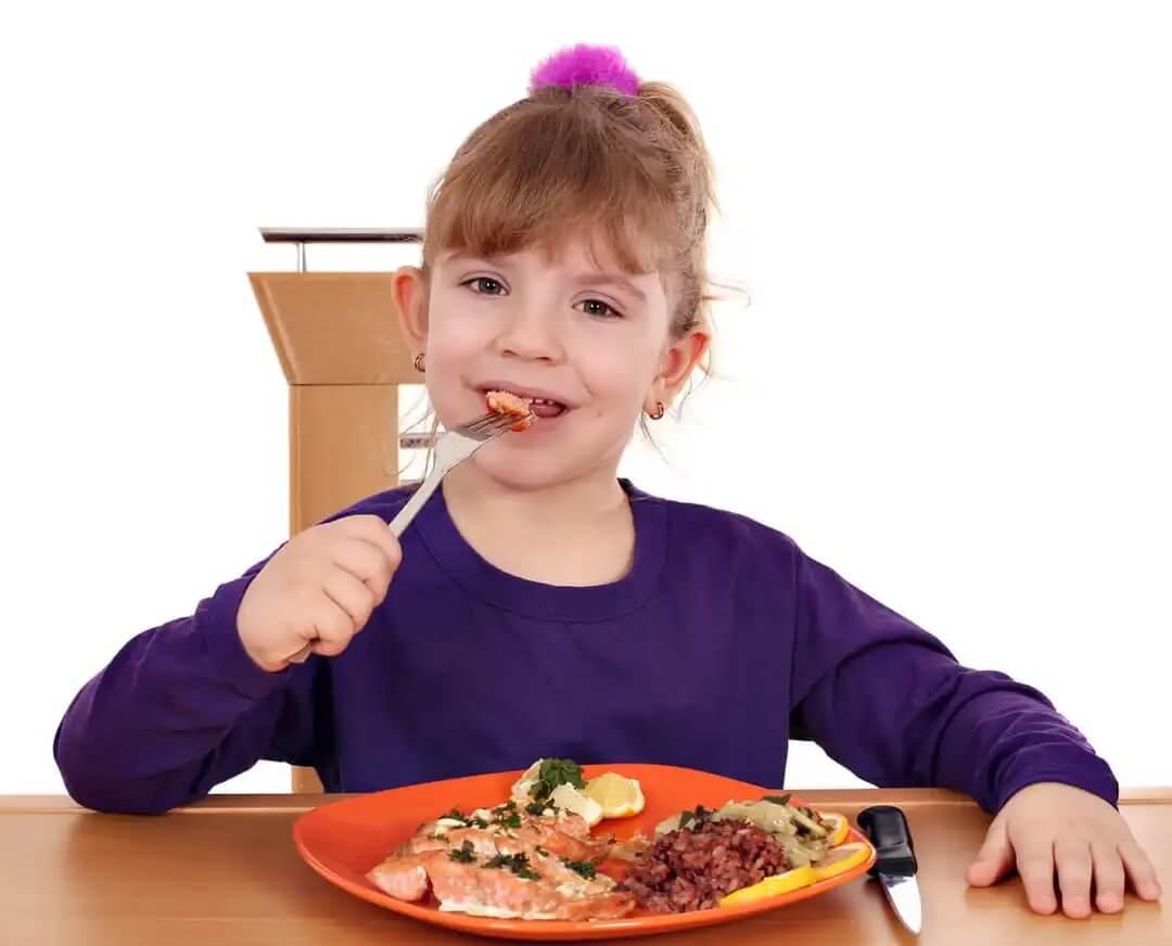 Menina comendo salmão, um dos alimentos que cuidam do coração da criança.
