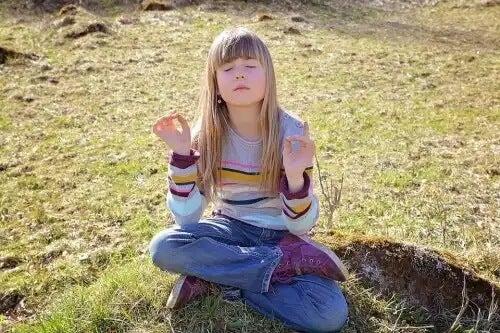 Criança meditando ao ar livre.