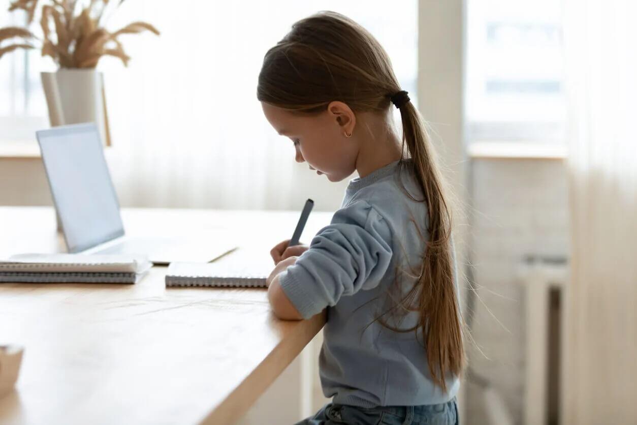 Menina fazendo lição de casa com boa higiene postural.