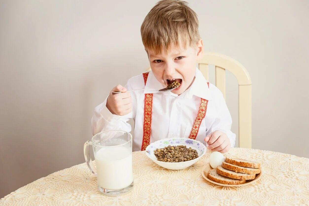 Criança comendo lentilhas porque as leguminosas são muito importantes.