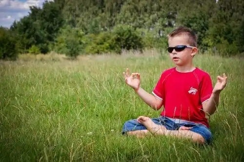 Menino meditando ao ar livre.