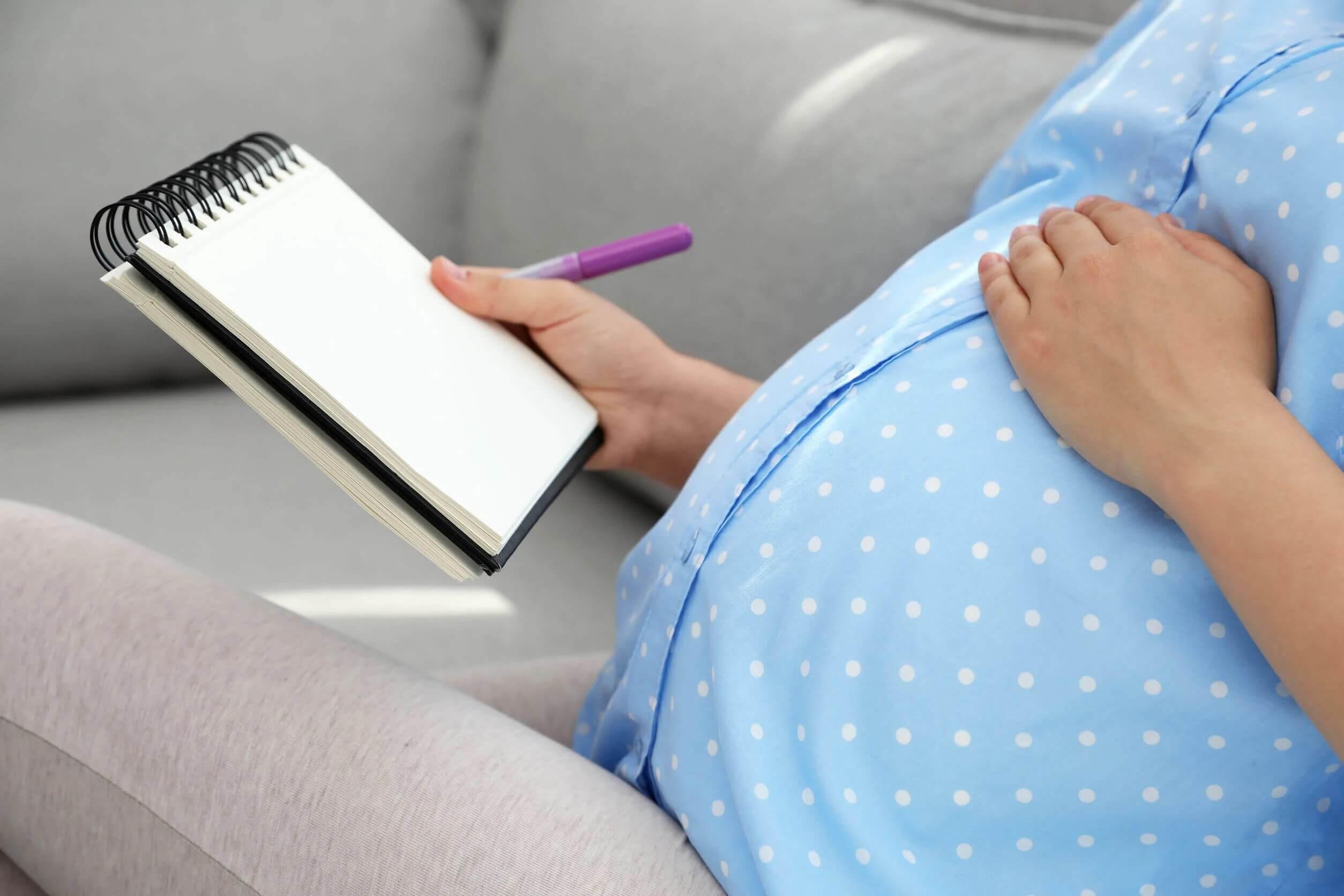 Mulher grávida pensando e escrevendo os nomes dos bebês élficos.