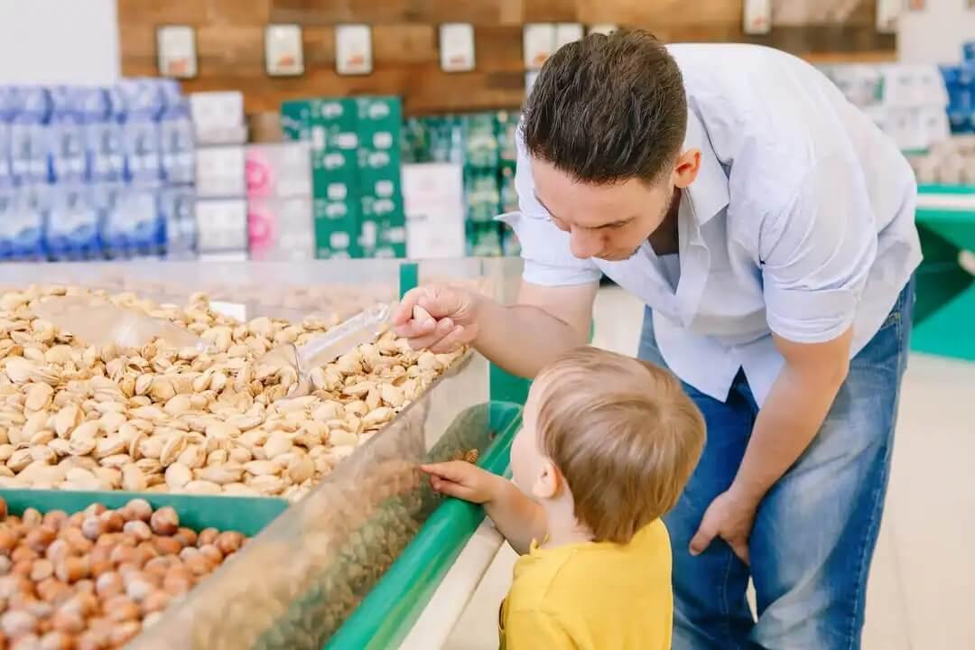 Pai com filho comprando nozes a granel.