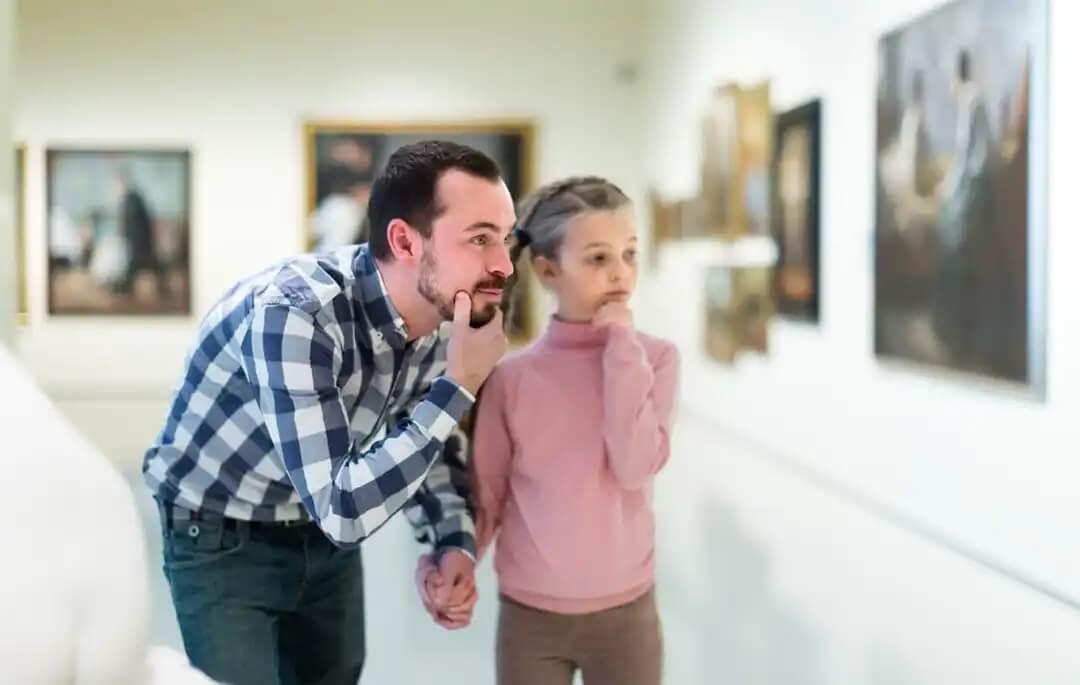 Pai e filha visitando um museu durante a Semana Internacional de Educação Artística.