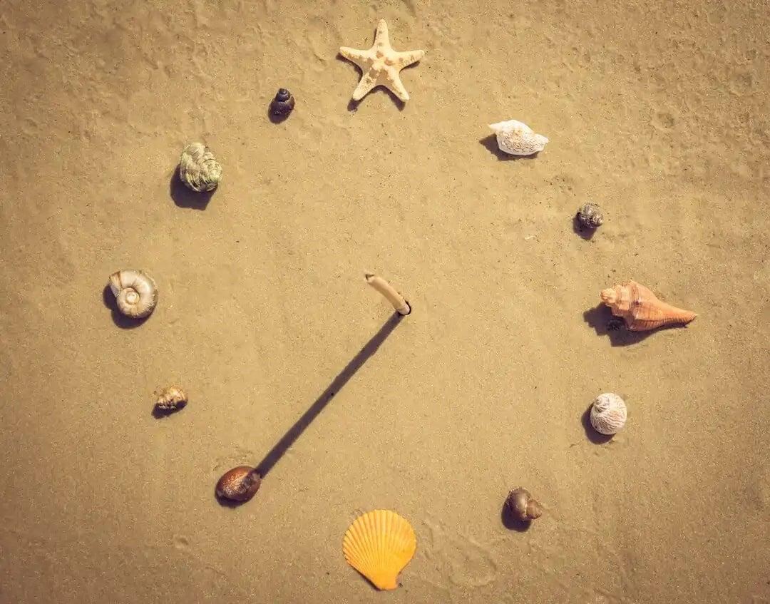 Relógio de sol caseiro na areia.