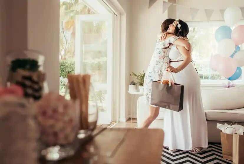 Amiga dando um abraço na futura mamãe no chá de bebê.