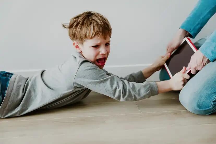 Menino gritando porque sua mãe tirou o tablet.