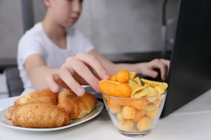 Criança comendo comida ultraprocessada enquanto joga no computador.