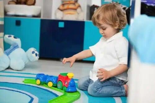 Menino de dois anos brincando com três sentado no chão.