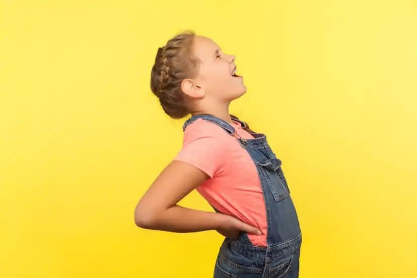 Menina com dor nos rins devido à retenção de urina.