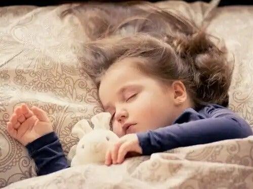 Criança dormindo com seu bichinho de pelúcia.