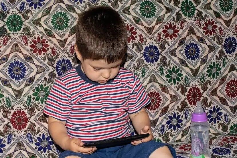 Criança assistindo filmes no tablet porque não consegue se desconectar das telas.
