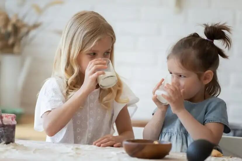 Raparigas a tomarem um copo de leite de acordo com a quantidade adequada para a idade.