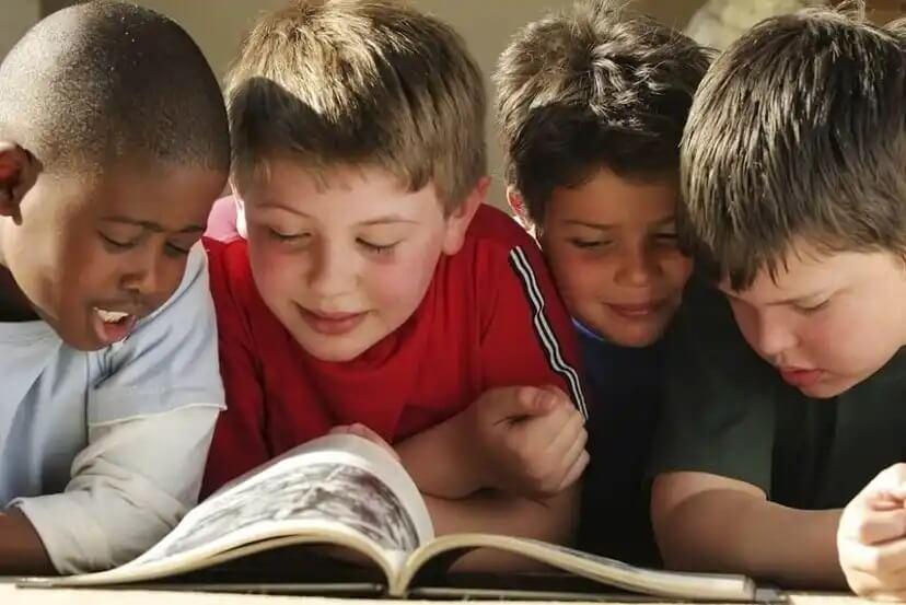 Crianças lendo uma história com ilustrações.