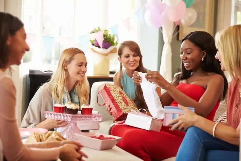 Amigas em um chá de bebê distribuindo presentes.