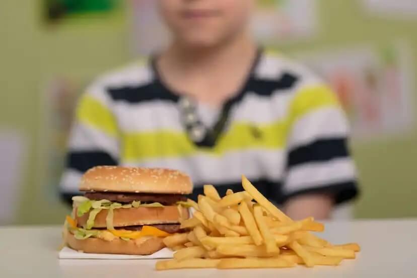 Criança comendo junk food.