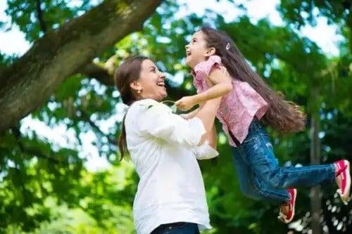 Mãe brincando com a filha no parque.