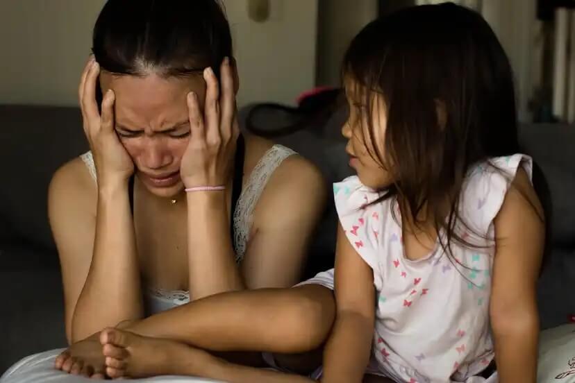Mãe chorando na frente da filha porque sofre de depressão.