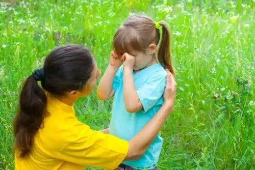 Mãe dizendo à filha algumas das frases para confortar as crianças quando elas estiverem chorando.