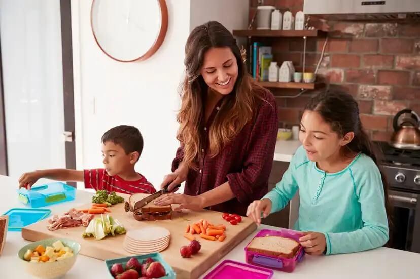 Mãe com seus filhos na cozinha preparando pratos saudáveis com todos os nutrientes necessários.