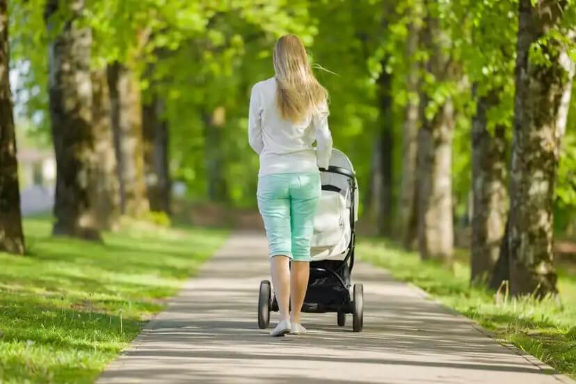 Mãe dando um passeio com seu bebê no parque.