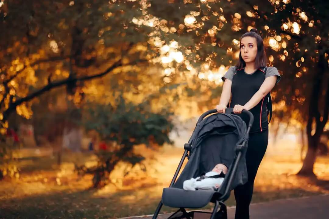 Mulher caminhando com seu bebê como parte da prática de exercício após o parto para se recuperar.
