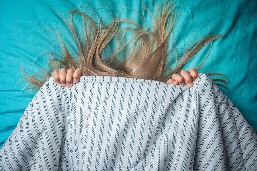 Menina coberta com o lençol porque tem medo de ter pesadelos.